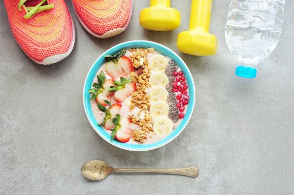 Bowl de comida sana junto a zapatos y pesas de entrenamiento