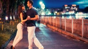 Pareja heterosexual bailando bachata en la calle.