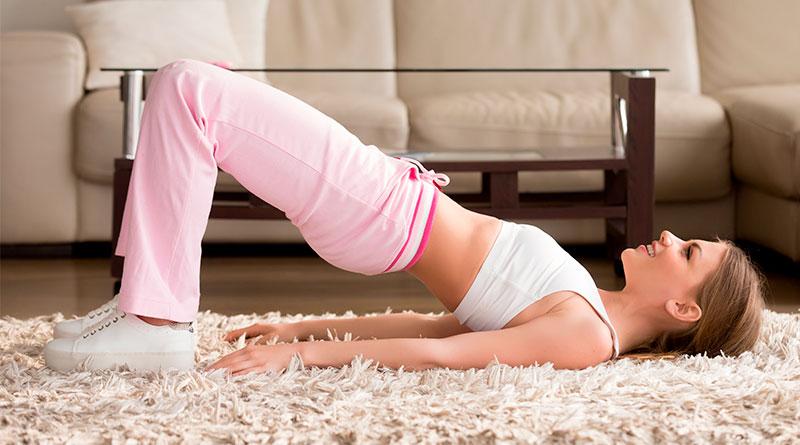 Mujer en la sala de su casa, realizando el ejercicio de elevación de cadera.