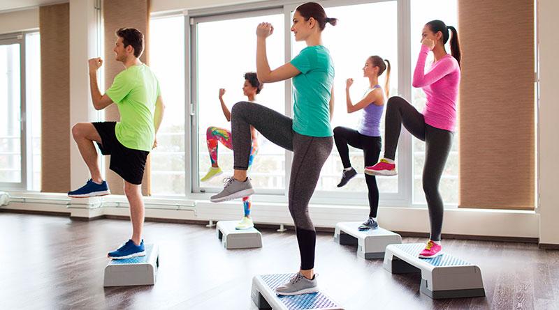 Mujeres practicando clase de step en el gimnasio.