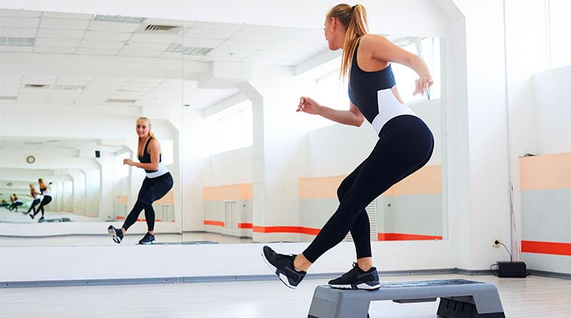 Mujer practicando la rutina de step con talón.