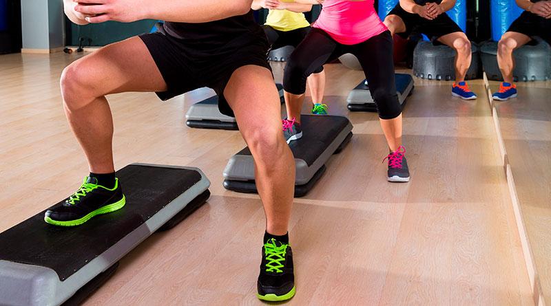 Personas en clase de step haciendo ejercicio de Caballo abajo.