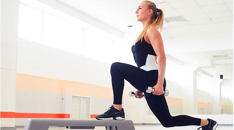 Mujer en el gimnasio usando step para hacer fondos.