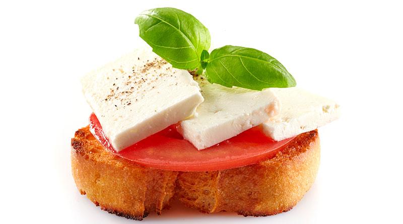Imagen de botana suiza de queso panela con jitomate en pan blanco.