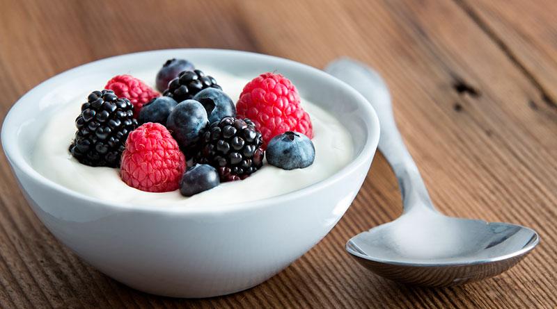 Imagen de plato hondo con moras azules y arándanos, combinados con yogurt griego.