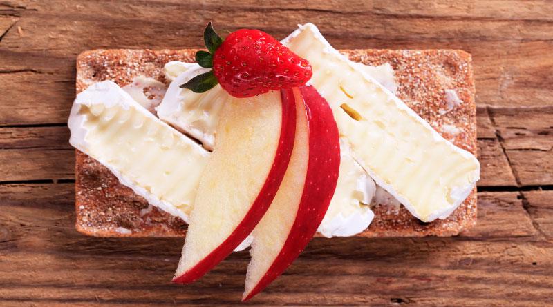 Imagen de manzana roja, fresa y queso panela, sobre un pan integral.