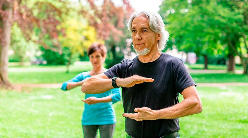 Hombre y mujer practicando Tai chi en el parque.