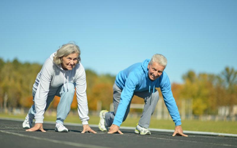 Dos adultos mayores preparándose para correr