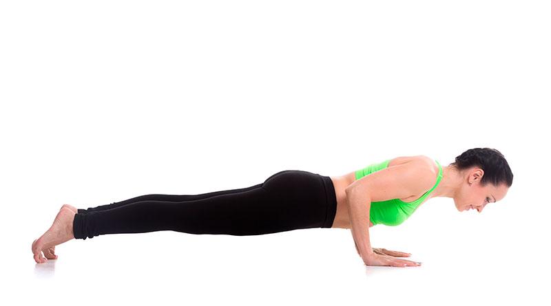 Mujer practicando postura de yoga Bastón de 4 miembros.