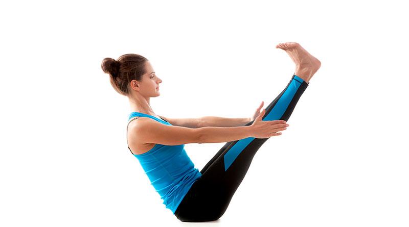 Mujer practicando la postura de yoga del barco.