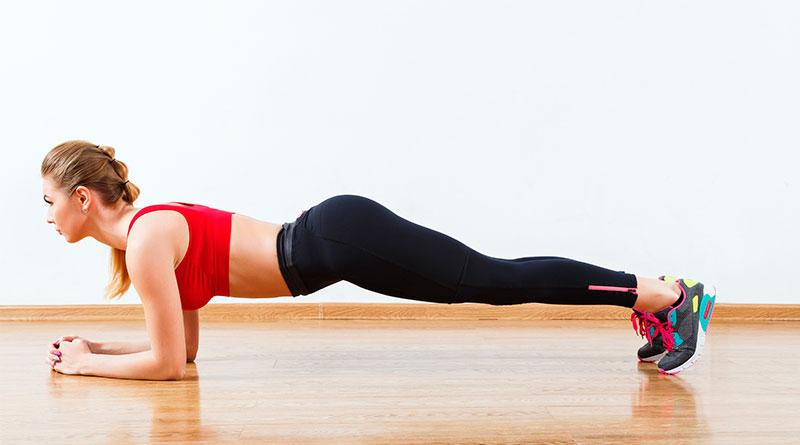 Mujer practicando la postura de yoga plancha con codos.