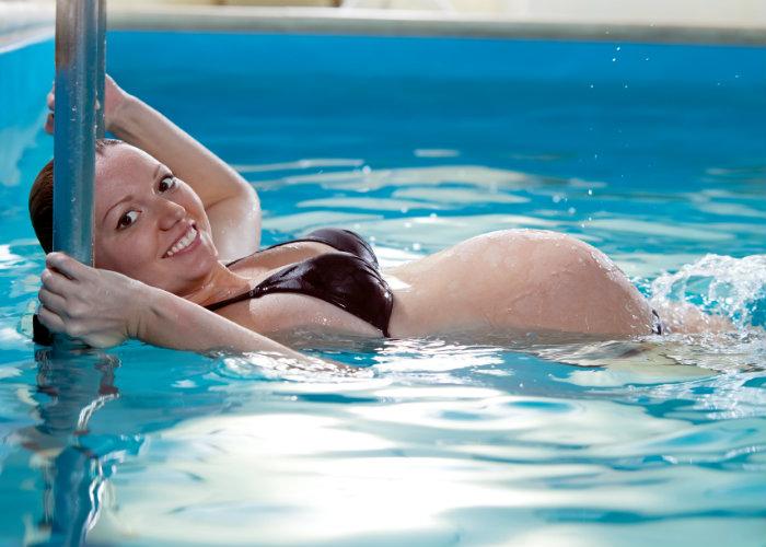 Mujer embarazada nadando voltea hacia a la cámara