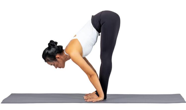 Mujer haciendo yoga tocando la punta de los pies